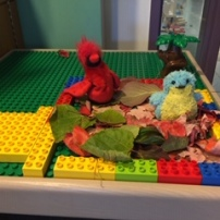 A cardinal and a bluebird sit together in their Lego nest
